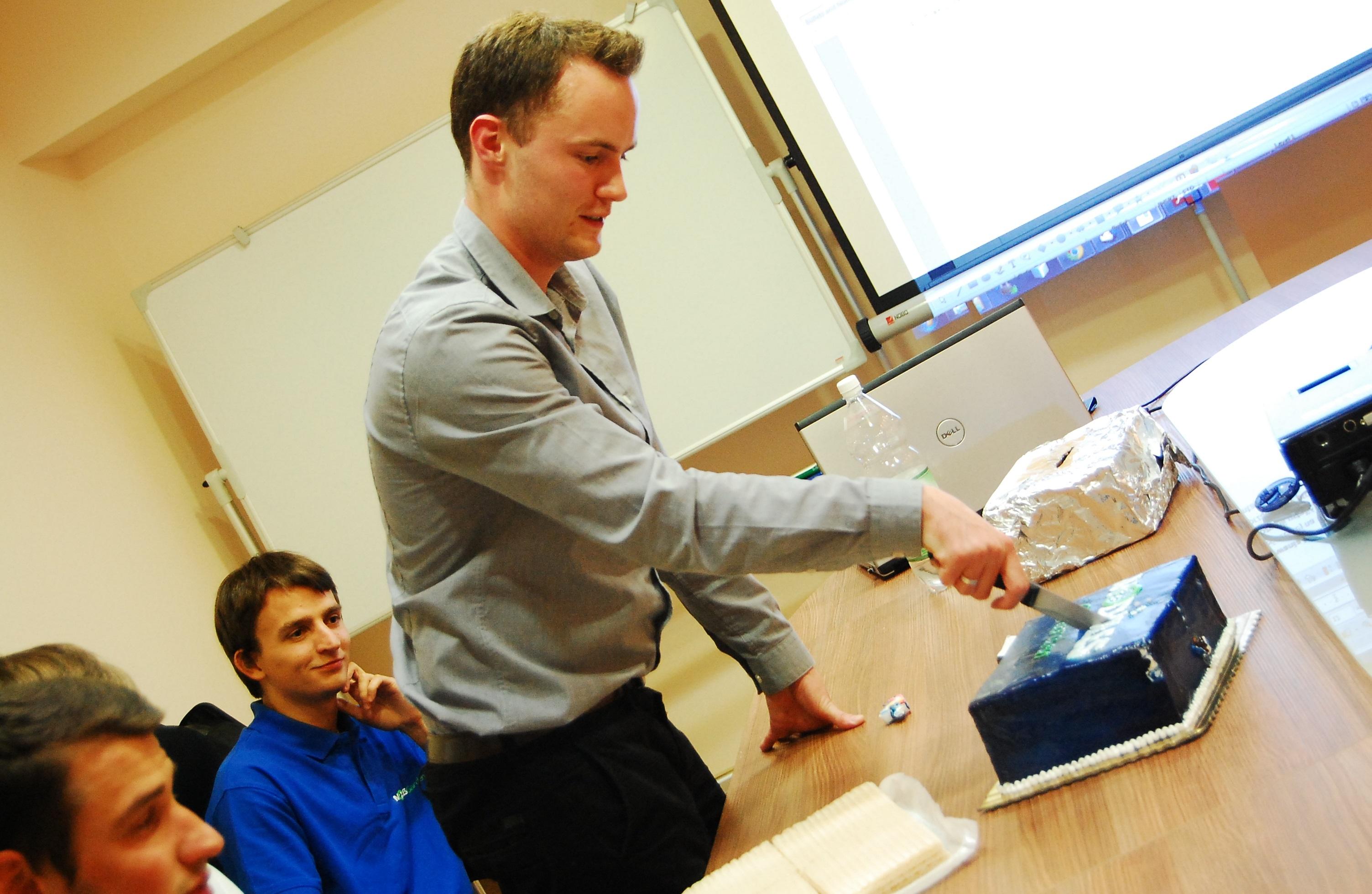 ModulesGarden CEO Konrad Keck Cutting A Cake